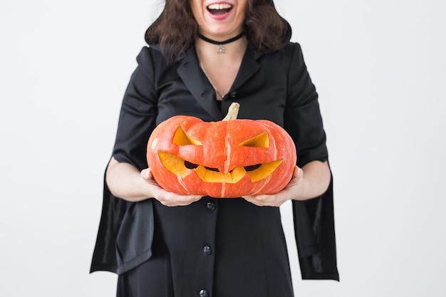 Halloween- und feiertagskonzept - hexenfrau mit jack o'lantern-kürbis.
