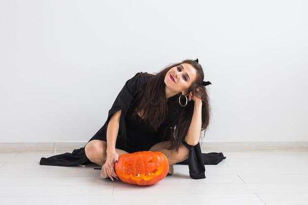 Halloween- und feiertagskonzept - hexenfrau mit jack o'lantern kürbis.