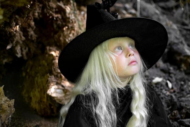 Halloween und hexen. kind im bild einer hexe mit weißen haaren in einer dunklen höhle, feiertag