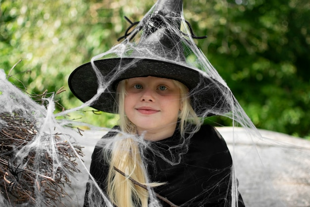 Halloween und kinder. mädchen in einem schwarzen hut mit spinnen und spinnweben, porträt