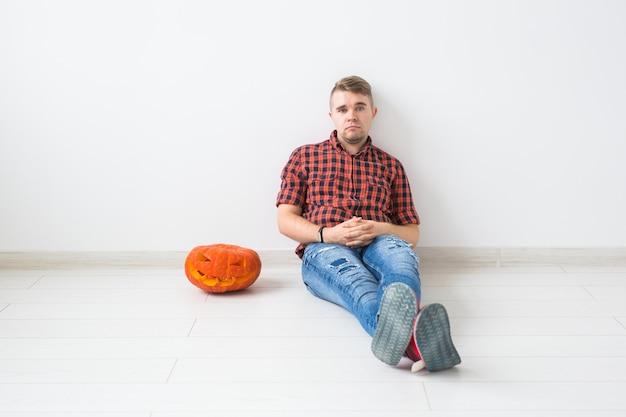 Halloween und maskerade-konzept - hübscher mann, der mit kürbis-jack-laterne aufwirft.