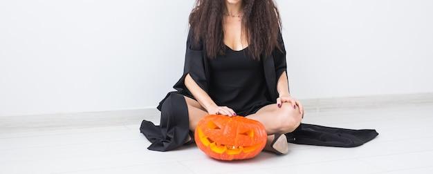 Halloween- und maskerade-konzept - schöne junge frau der nahaufnahme, die mit kürbis-kürbislaterne aufwirft