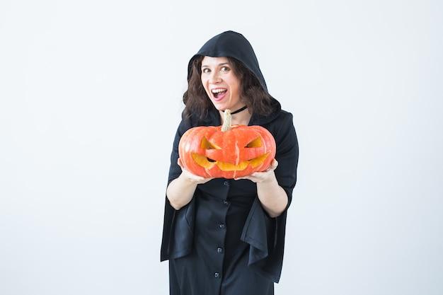 Halloween- und maskerade-konzept - schöne junge frau, die mit kürbis-kürbislaterne aufwirft