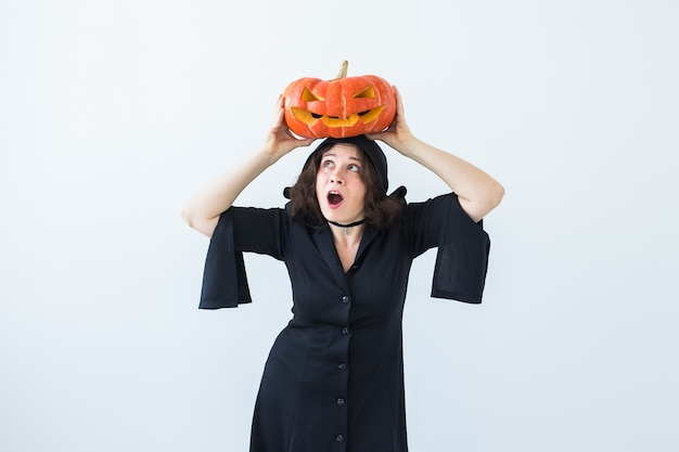 Halloween- und maskerade-konzept - schöne junge frau, die mit kürbis-kürbislaterne aufwirft Premium Fotos