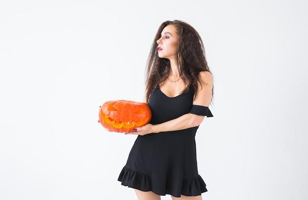 Halloween und maskerade-konzept - schöne junge frau posiert mit kürbis jack-o'-laterne.