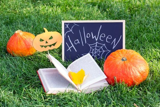 Halloween urlaub. kürbisse, ein zauberbuch und ein schild mit der aufschrift: halloween