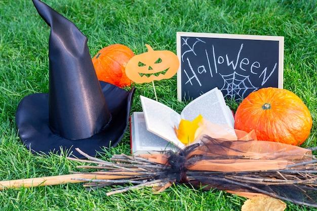 Halloween urlaub. kürbisse, hexenhut, besenstiel, zauberbuch und halloween-zeichen