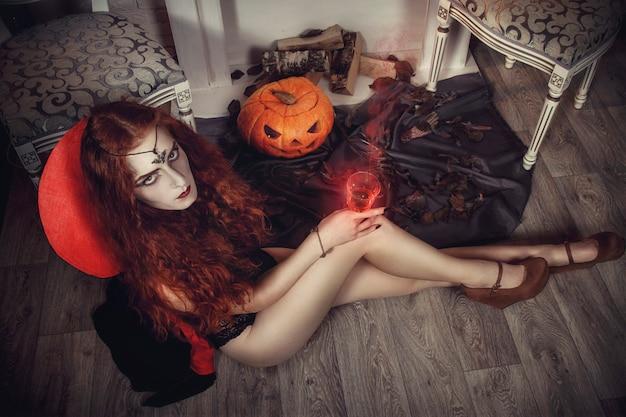 Halloween weibliche hexe bereitet sich auf das fest der toten vor. rothaarige schwarzmagierin. mystische hexerei