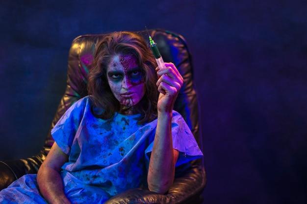 Halloween-zombie-frau, die eine giftspritze hält
