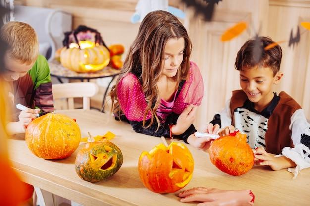 Halloweenkostüm. schöne gut aussehende jungen und mädchen, die halloween-kostüme tragen, die sich erstaunlich fühlen