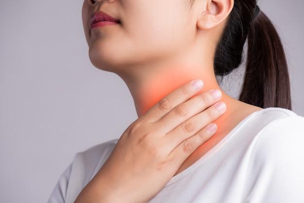 Halsentzündung. nahaufnahme der schönen jungen frau hand, die ihren hals berührt