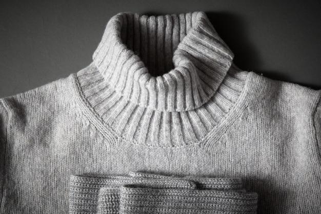 Halsgrauer strickpullover und strickschal gefaltet