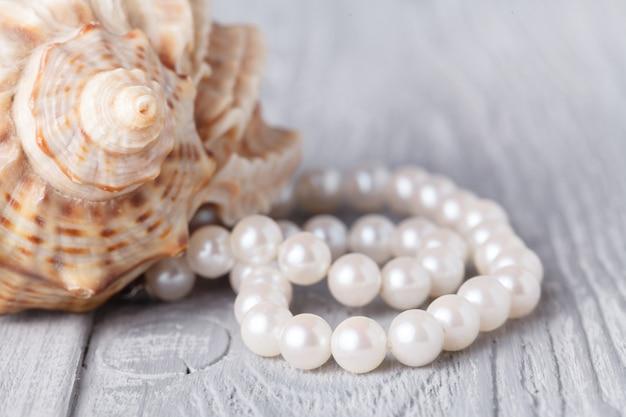Halskette aus perlen und muschel auf weißem holz