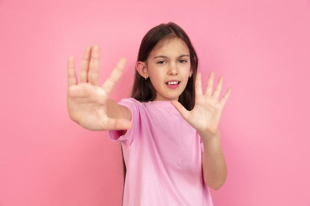 Halt, angst. kaukasisches porträt des kleinen mädchens lokalisiert auf rosa studiohintergrund. nettes brunettemodell im hemd. konzept der menschlichen emotionen, gesichtsausdruck, verkauf, anzeige, kindheit. exemplar.