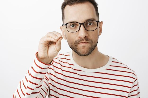 Halt die klappe. porträt eines verärgerten wütenden freundes in einer schwarzen brille, der an den lippen saugt und die stirn runzelt, eine schweigegeste zeigt und sich empört fühlt