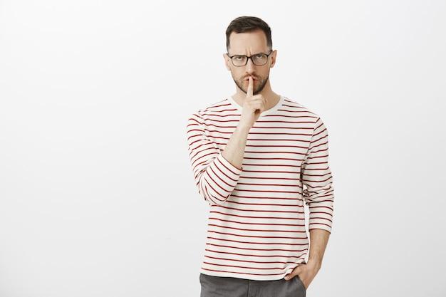 Halt die klappe, shh. porträt eines streng missfallenen männlichen lehrers in einer schwarzen brille, der die stirn runzelt und unter der stirn hervorschaut, mit dem zeigefinger über dem mund eine shush-geste macht und die hand in der tasche hält