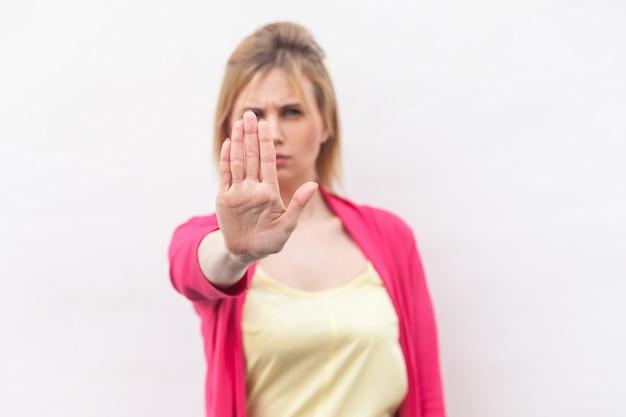 Halt. porträt einer ernsten blonden jungen frau in gelbem hemd und roter bluse, die mit der hand eine stoppgeste zeigt. fokus auf die hand. indoor-studioaufnahme, isoliert auf weißem wandhintergrund.