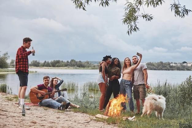 Halte den moment fest. eine gruppe von menschen hat ein picknick am strand. freunde haben spaß am wochenende.