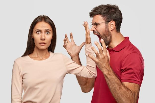 Halte den mund, halt den rand, halt die klappe! verwirrte schöne frau hält handfläche nahe dem mund des mannes