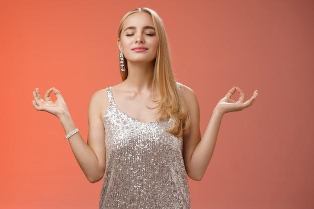 Halte die ganze nacht eine ruhige party. sorglose ungestörte glückliche charmante stressfreie blonde junge frau in stilvollem kleid lächelnd erleichtert enge augen freuen sich stehende lotus nirvana pose, atmung meditieren.