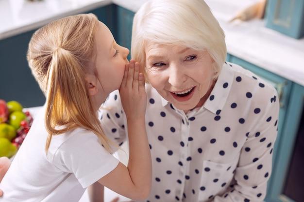 Halte mein geheimnis. hübsches kleines mädchen, das ihrer großmutter ins ohr flüstert und ihre geheimnisse mit ihr teilt, während die frau amüsant lächelt