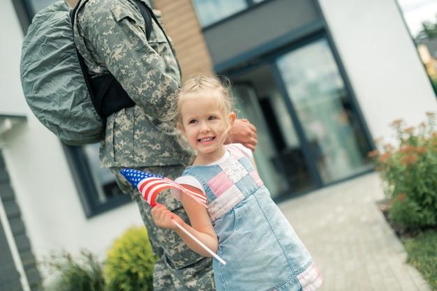Halten der amerikanischen flagge. schönes mädchen mit amerikanischer flagge, das mit ihrem helden nach hause geht, der nach hause zurückkehrt?