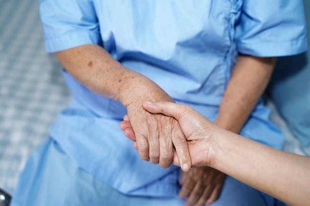 Halten der rührenden hände asiatinpatient mit liebe