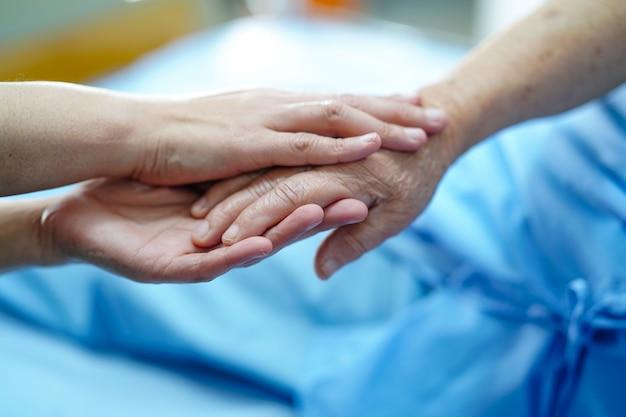 Halten der rührenden hände asiatischer älterer oder älterer frauenpatient der alten dame mit liebe