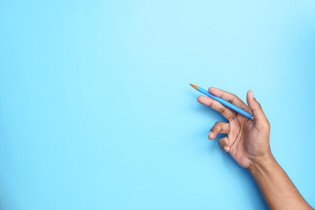 Halten des blauen farbstifts gegen blaue wand