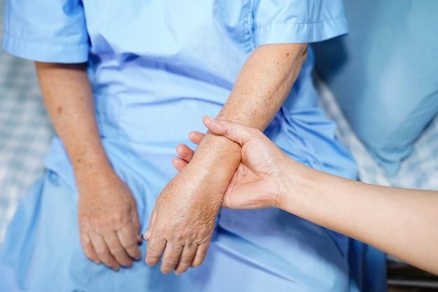Halten des rührenden handasiatischen älteren frauenpatienten mit liebe.