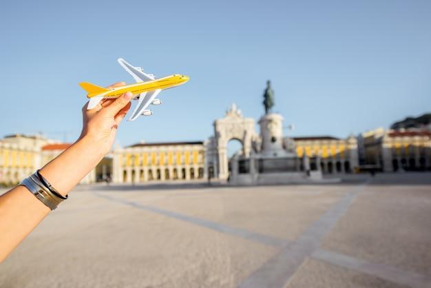 Halten ein spielzeugflugzeug auf dem zentralen platz mit triumphbogen im hintergrund in der stadt lissabon, portugal