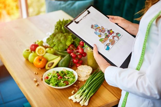 Halten eines schematischen speiseplans für eine diät mit verschiedenen gesunden produkten im hintergrund