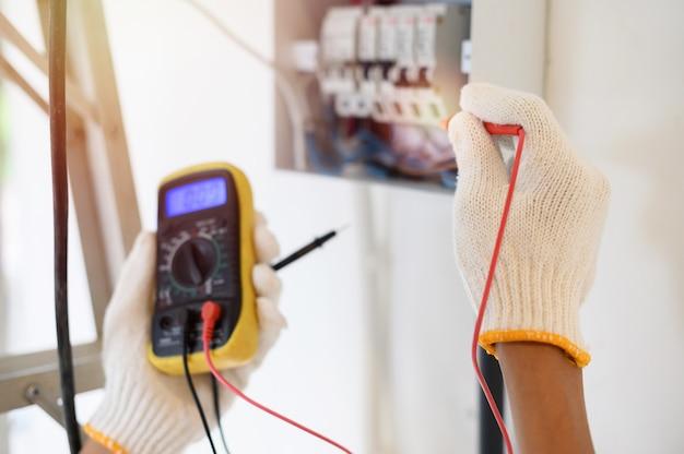 Halten sie das digitalmultimeter gedrückt, um den elektrischen strom am schalter zu überprüfen. konzentriere dich auf eine behandschuhte hand.
