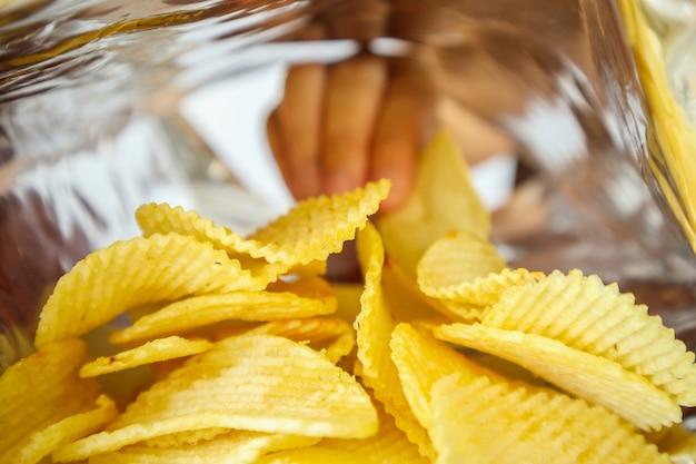 Halten sie die kartoffelchips in der hand im snackfolienbeutel