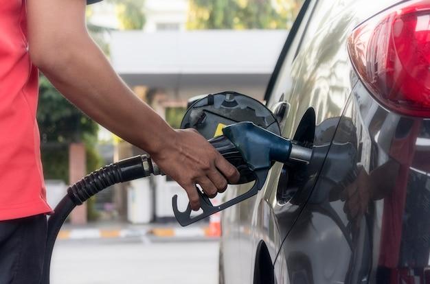 Halten sie die kraftstoffdüse fest, um kraftstoff an der tankstelle in das auto zu füllen