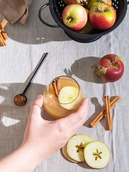 Halten sie ein glas frisch gebrühtes apfelgetränk mit apfelscheiben und zimt auf der leinentischdecke in der hand. draufsicht und flach liegen