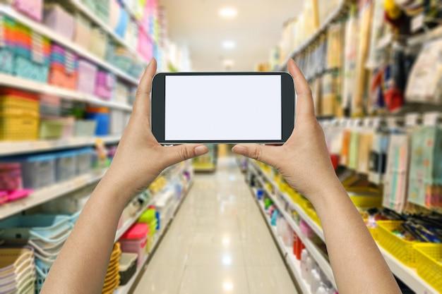 Halten sie ein smartphone in der hand, um im supermarkt geld zu kaufen oder zu bezahlen. technologiekonzept.