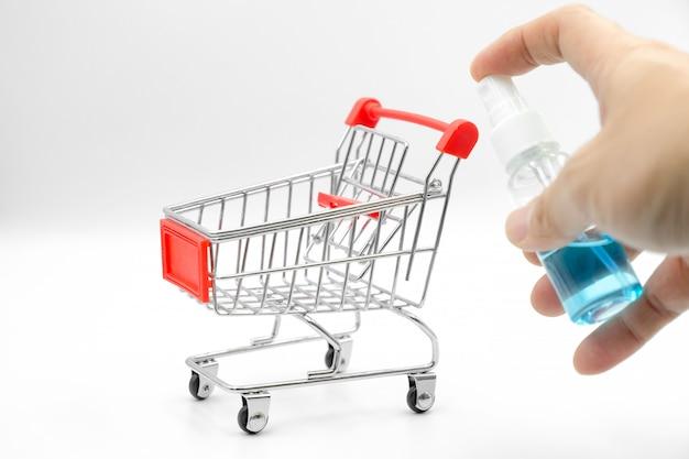 Halten sie eine alkoholsprühflasche zur desinfektion am griff des supermarktwagens, um sich vor schmutz und bakterien zu schützen.