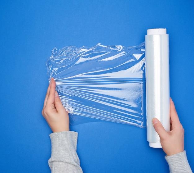 Halten sie eine große rolle gewickelter weißer transparenter folie zum einwickeln von lebensmitteln in die hand