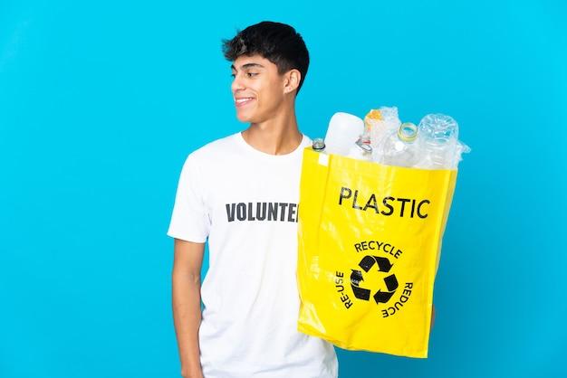 Halten sie eine tasche voll plastikflaschen, um über blaue seite aussehende wand zu recyceln