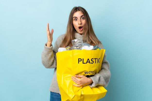 Halten sie eine tasche voller plastikflaschen, um sie mit überraschendem gesichtsausdruck über blau zu recyceln