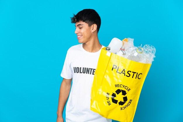 Halten sie eine tasche voller plastikflaschen, um über blaue wand zu recyceln, die zur seite schaut und lächelt