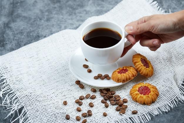 Halten sie eine tasse kaffee mit keksen und kaffeebohnen.