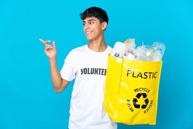 Halten sie eine tüte mit plastikflaschen zum recyceln über die blaue wand, um die lösung zu erkennen, während sie einen finger nach oben heben
