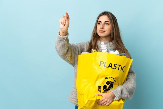 Halten sie eine tüte voll plastikflaschen, um auf isoliertem blau zu recyceln, das auf transparentem bildschirm berührt