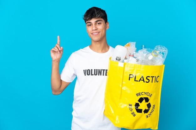 Halten sie eine tüte voll plastikflaschen, um sie auf blauem papier zu recyceln, und heben sie einen finger, um das beste zu zeigen