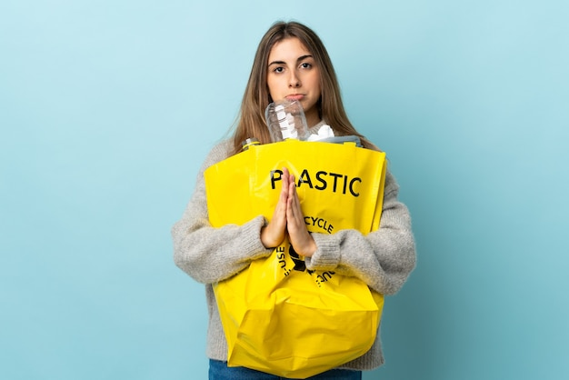 Halten sie eine tüte voll plastikflaschen, um über isoliertes blaues plädoyer zu recyceln