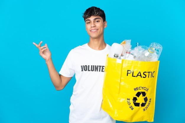 Halten sie eine tüte voller plastikflaschen, um sie über die blaue wand zu recyceln, und strecken sie die hände zur seite, um sie einzuladen