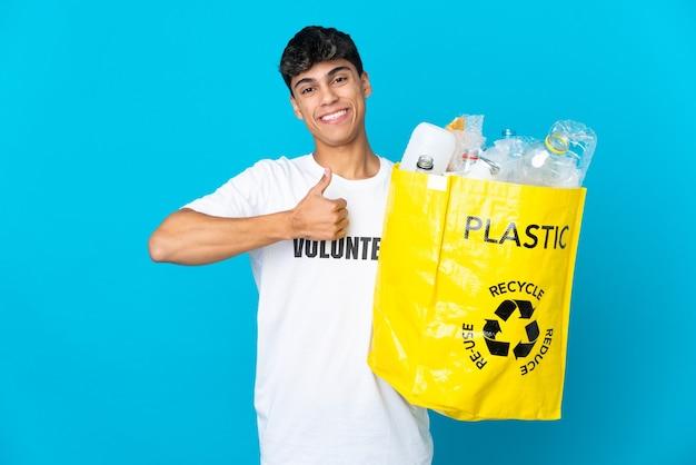 Halten sie eine tüte voller plastikflaschen, um sie über die blaue wand zu recyceln, und zeigen sie mit dem daumen nach oben
