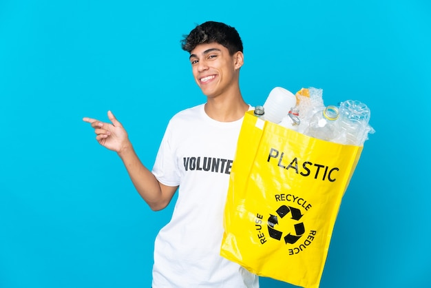 Halten sie eine tüte voller plastikflaschen, um sie über die blaue wand zu recyceln, und zeigen sie mit dem finger zur seite, um ein produkt zu präsentieren